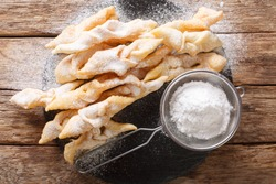 Freshly made Angel Wings Cookies with powdered sugar close-up on the table. horizontal top view from above