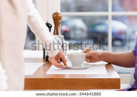 Freshly-made coffee. Waitress brings a cup of freshly made double espresso and puts it in front of the client.
