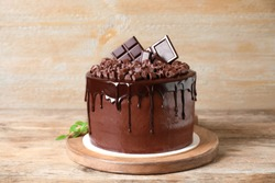 Freshly made delicious chocolate cake on wooden table