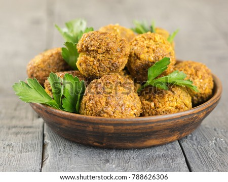 Freshly made falafel in a clay bowl with herbs on a dark wooden table.