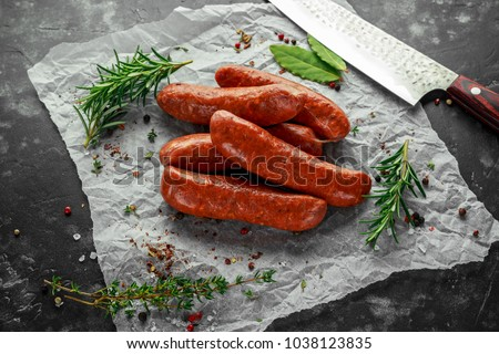Freshly made raw breed butchers sausages in skins with herbs on crumpled paper. Foto d'archivio ©