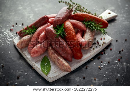 Freshly made raw breed butchers sausages mix in skins with herbs on white cutting board. Foto d'archivio ©