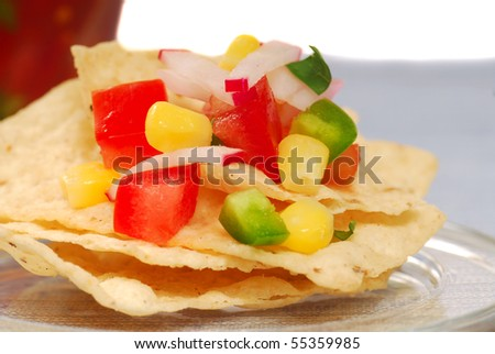 Freshly made tortilla chips with a corn and tomato salsa