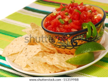 Freshly made tortilla chips with a corn and tomato salsa with limes