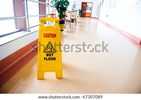 freshly mopped hallway with a caution sign in English.