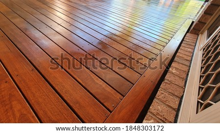 Freshly oiled Australian spotted Gum timber outdoor covered deck with Merbau stain at Residential Home, still wet and yet to dry Foto stock ©