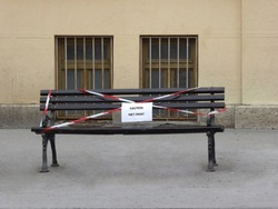 Freshly painted bench at the street with a sign CAUTION WET PAINT