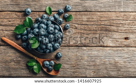 Freshly picked blueberries in bowl on wooden background. Healthy eating and nutrition.