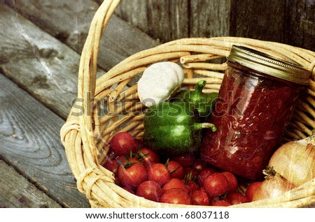 Freshly picked organic vegetables and a jar of homemade salsa on a rustic background, grunge textured. - stock photo