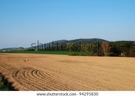 Freshly ploughed filed in the spring and a rural landscape
