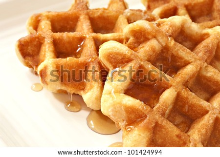 Freshly prepared belgian waffles with maple syrup on cream colored serving plate.  Macro with shallow dof.