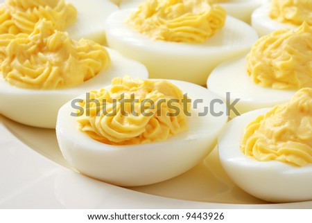 Freshly prepared deviled eggs on a porcelain plate.  Macro with extremely shallow dof.  Focus on front eggs.  Ideal as background.