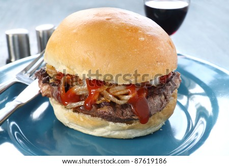 Freshly prepared fillet steak burger with fried onions and ketchup