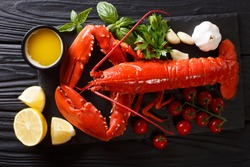 Freshly prepared lobster closeup with lemon, garlic, fresh tomatoes and herbs on a black table. horizontal top view from above