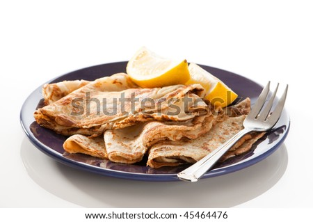 Freshly prepared pancakes for Shrove Tuesday with wedges of lemon - stock photo