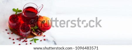 freshly prepared pomegranate juice in a decanter and two glasses on a marble table and a gray stone background with mint leaves and fruit seeds #1096483571