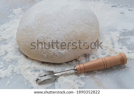 Freshly risen classic French boule bread dough on a marble pastry board with a lame, getting ready for scoring Photo stock ©