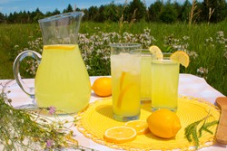 Freshly squeezed lemonade beverage and sliced lemons in a pitcher with ice cubes in summer