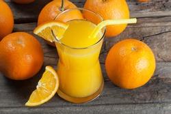 freshly squeezed orange juice in glass with orange fruits on wooden background, bitter seville fresh oranges citrus fruit concept