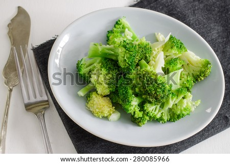 Freshly steamed broccoli served with small plate with fork and napkin on white table