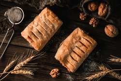 Freshly sweet puff pastry buns with jam on slate sackcloth background with wheat spikelets and walnut. Pastries and bakery, top view