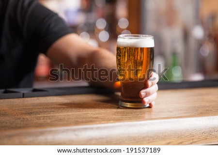 Freshly tapped beer. Bartender holding a freshly tapped glass of beer in his hand #191537189