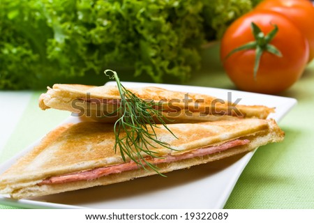 Freshly toasted cheese and ham sandwich with lettuce