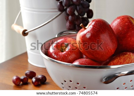 Freshly washed apples in colander with bucket of grapes in background.  Closeup with shallow dof.