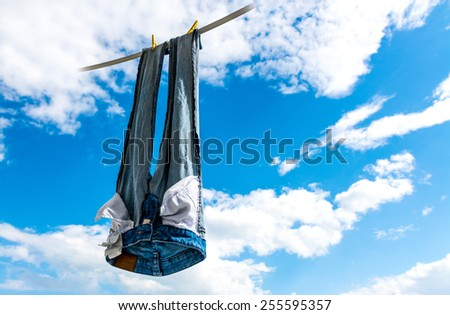 Freshly washed blue jeans on let to dry in the sky. Detergent commercial concept.