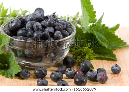 Freshly washed blueberries in glass bowl on wood cutting board with fresh herbs in background