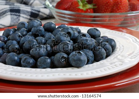 Freshly washed blueberries on a plate with strawberries in the background.  Red, white and blue color theme.  Close-up with shallow dof. - stock photo