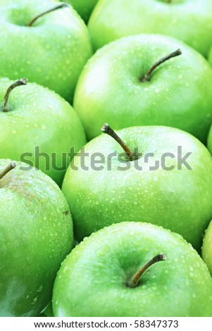 Freshly washed green apples lined up neatly. Selective focus on second apple from the bottom.