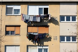 Freshly washed laundry left to dry on warm winter sun on edge of apartment windows of old apartment building with dilapidated light yellow facade surrounded with tall trees without leaves