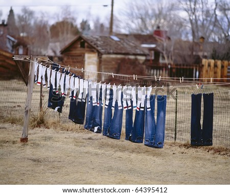 Freshly washed socks and pants hanging out to dry on a clothesline.