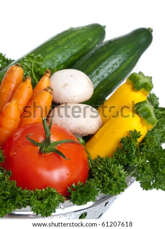 Freshly washed vegetables in strainer on pure white background