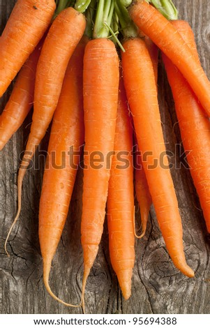 Freshly washed whole carrots on old wooden table