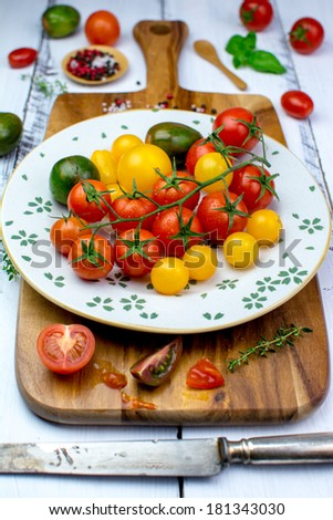 Freshly washed yellow, red, green and black tomatoes, herbs, salt and pepper and a rusty knife on a vintage plate on a wooden cutting board