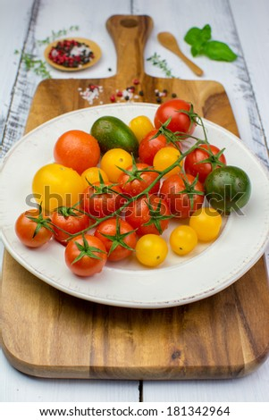 Freshly washed yellow, red, green and black tomatoes, herbs, salt and pepper on a vintage plate on a wooden cutting board