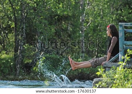 Freshness! Girl playing with river splashes.