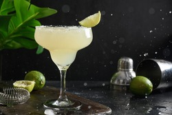Freshness splash and Margarita cocktail with lime and salt on a black background. Freshness summer alcoholic beverage for festive home party.