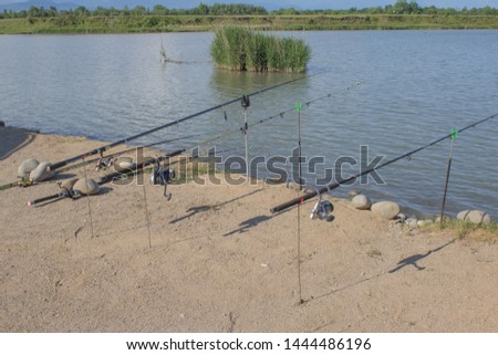 Freshwater angling with rods beside a lake. A reel fishing rod on a prop and water background