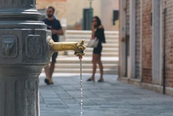 Freudian allusions. Leaking tap, young woman in miniskirt  looking in the wake of passing by man. Venice, Italy.