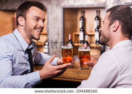 Friday night fun Two cheerful young men in shirt and tie talking to each other and gesturing while drinking beer at the bar counter