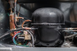 Fridge compressor condenser, close-up. Refrigerator backside including corroded copper pipes, electrical wiring and dust and pet hair. Concept for maintaining and repair appliances. Selective focus