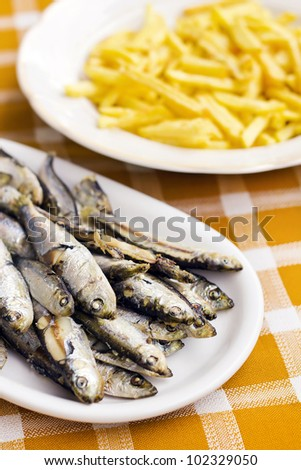 Fried anchovies and french fries (selective focus)