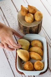 Fried and roasted Brazilian savorys. Woman's hand picking up one of the savory.