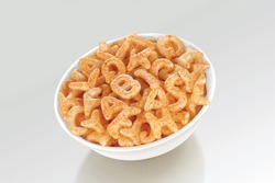 Fried and Spicy ABCD, Alphabet Snacks or Fryums (Snacks Pellets) served in a white bowl. selective focus - Image