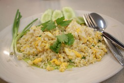Fried and stirred cooked rice with chicken egg topping with coriander on the plate. Famous fast food menu in Asia restaurant. Quick meal in rush hour concept.