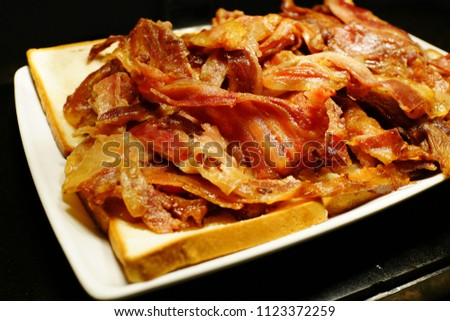 Free photos Strips of crispy fried bacon on a slice of bread