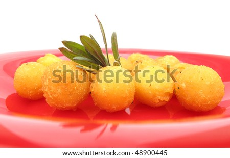 Fried balls on red plate with lavender